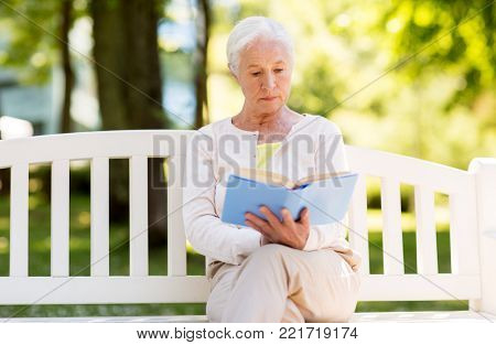 old age, retirement and people concept - senior woman reading book sitting on bench at summer park