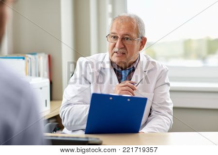medicine, healthcare and people concept - senior doctor with clipboard talking to young male patient having health problem at hospital