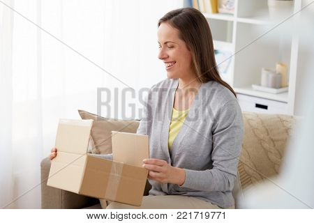 delivery, mail and people concept - smiling middle-aged woman opening parcel box at home
