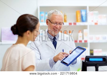 medicine, healthcare and technology concept - senior apothecary and female customer with digital prescription on tablet pc computer screen at pharmacy