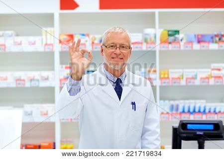 medicine, healthcare and people concept - senior apothecary at pharmacy cash register showing ok hand sign