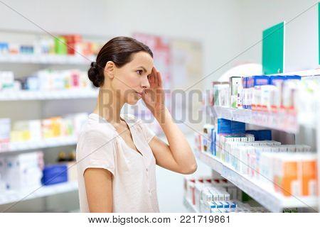medicine, pharmaceutics, healthcare and people concept - female customer having headache choosing drugs at pharmacy
