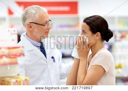 medicine, healthcare and people concept - senior apothecary with drug and female customer having cold and blowing nose at pharmacy
