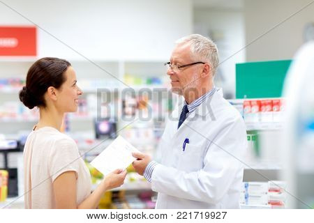 medicine, healthcare and people concept - female customer giving prescription to senior apothecary at pharmacy