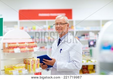 medicine, healthcare and technology concept - senior apothecary with tablet pc computer at pharmacy