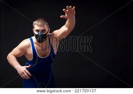 A young dark-haired man fighting Greco-roman wrestling and grappling in a blue   tights  , training mask  posing against a black isolated  background