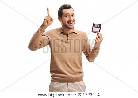 Young man with a floppy disk holding his index finger up isolated on white background
