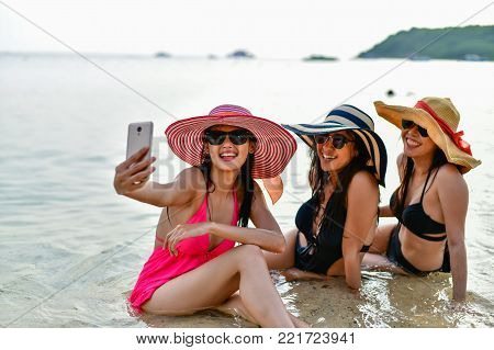 Swimsuit Concept. Beautiful girl wearing a swimsuit playing mobile on the beach. Beautiful girl is traveling on the beach. Beautiful girls are happy.