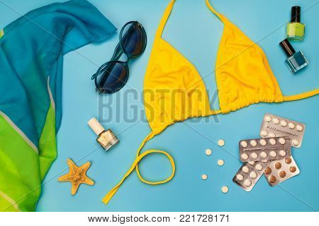 Summer women's beach accessories for your sea holiday and pill on blue background. Concept of medication required in journey. Top view.