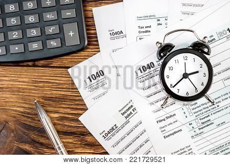 Tax forms with clock, pen and calculator on the office wooden table. Top view. Business and tax concept.