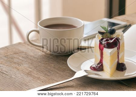 Blueberry cream cake on white plate. Delicious blueberry cake on wood table near window. Vanilla sponge cake decorated with dairy whipped cream and blueberry sauce so soft sweet and delicious. Homemade bakery background. Blueberry cake ready to served.