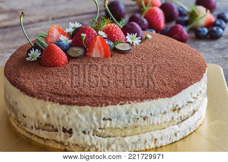 Round Tiramisu Cake On Wood Table Sprinkle With Cacao Powder And Decorated With Fresh Fruits. Italia