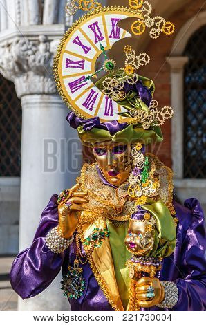 VENICE, ITALY -  FEBRUARY 27, 2014: Carnival of Venice. Carnival mask with clock on his head on street during celebration of famous carnival of Venice.