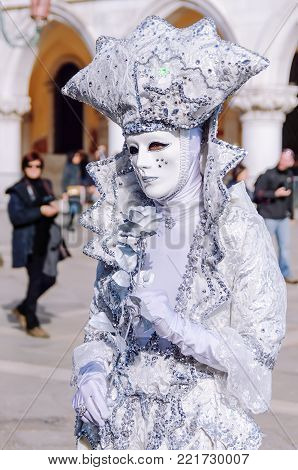 VENICE, ITALY -  FEBRUARY 27, 2014: Carnival of Venice. Person in white costume with rose in St. Mark's Square during Carnival of Venice.