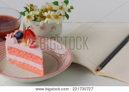 White chocolate strawberry yogurt cake decorated with fresh fruits and chocolate chunk. Sweet pink cake on wood table near notebook. Delicious and sweet pink cake for Valentines or birthday. Homemade bakery concept of strawberry cake. Sweet dessert.
