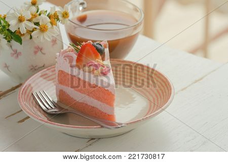 White chocolate strawberry yogurt cake decorated with fresh fruits and chocolate chunk. Sweet pink cake on white wood table near window. Delicious and sweet pink cake for Valentines or birthday party. Homemade bakery concept. Strawberry cake ready to serv