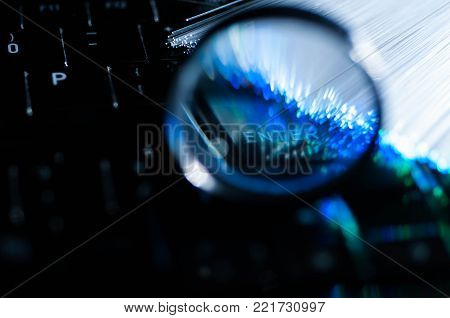 Magnifying glass on laptop keyboard enter word , conceptual internet searching image, blue green optical fibres.