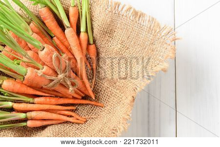fresh carrot, baby carrot on sack and white wood background and top view, This vegetable is an exceptionally rich source of carotenes and vitamin-A