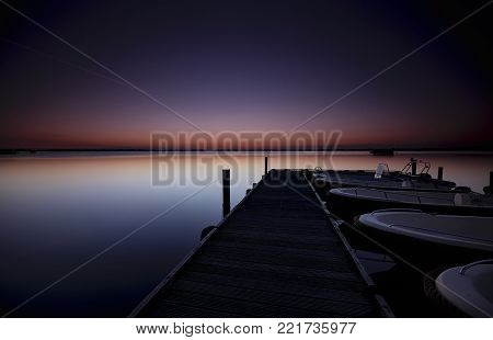 Motorboats docked at a wooden jetty in a quiet lake just before sunrise