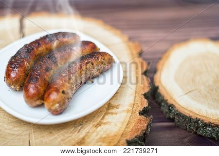 Grilled sausages grilled on a wooden table. Appetizing sausages, junk food.