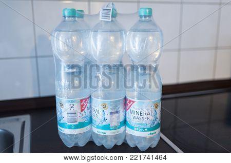 illustrative editorial of sixpack of 1.5 liter nonrefillable PET deposit bottles of EDEKA sparkling mineral water in shrink wrap on kitchen counter taken in Hamburg, Germany on 01/13/2018