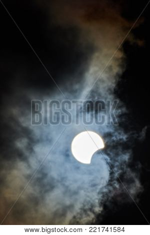 Start of full solar eclipse on cloudy sky background