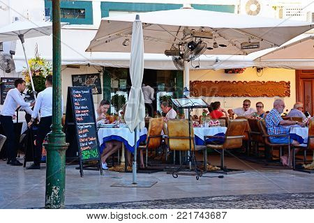 ALBUFEIRA, PORTUGAL - JUNE 6, 2017 - Tourists relaxing at a restaurant in the old town, Albufeira, Algarve, Portugal, Europe, June 6, 2017.