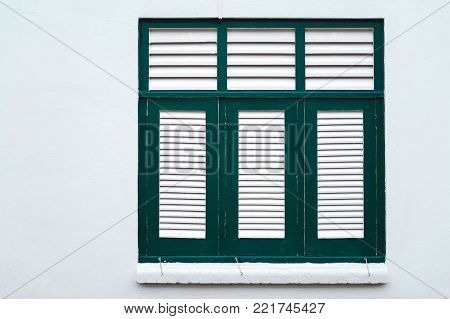 A simple window in Singapore. Shutters, the facades of historic buildings in Asia  simple window in Singapore. Shutters, the facades of historic buildings in Asia