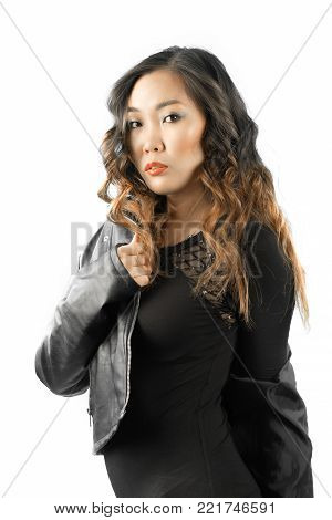 Full Lenght Portrait Of Asian Woman In Black Dress And Boots Standing And Swinging Her One Leg Up