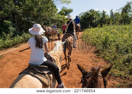 Vinales, Cuba - december 5, 2017: Cohabitation between tourists on horseback and Cubans with the wagon in the valley of Vinales (Cuba)