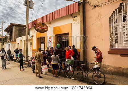 Santa Clara, Cuba - 10 dcember 2017: Cuban people waiting outside the bar to buy a cappucino