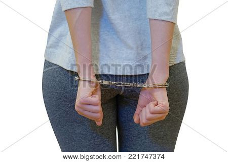 Close-up. Arrested woman handcuffed hands at the back. Prisoner or arrested terrorist, close-up of hands in handcuffs, selective focus. Isolated on a white background.