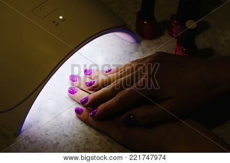 Two woman hand inside lamp for nails on table close up. UV lamp for drying nails with gel method. violet nails dried in the lamp