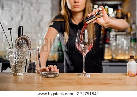 elegant barmaid preparing cocktails in a bar for her clients - Bartender at work in a club
