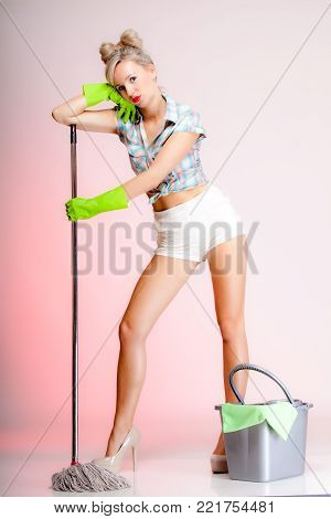 Full length sexy girl retro style with mop, woman housewife cleaner in domestic role. Traditional sharing household chores.  Pin up housework.  Pink background poster