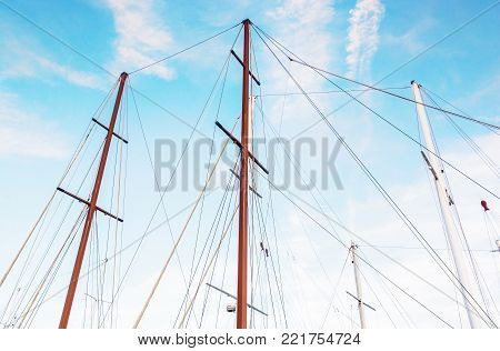 Masts of sailboat and blue sky. Summer vacation. Transport theme. Beauty photo filter.