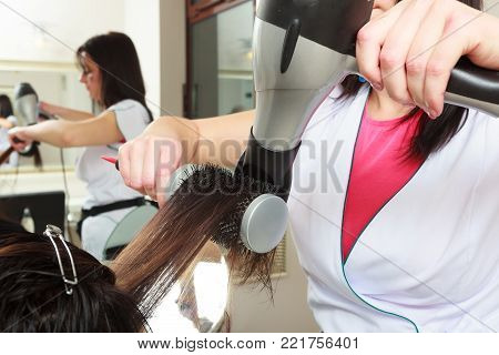 Hairstylist with brush and dryer. hairdresser drying hair of female client. Woman in hairdressing beauty salon.