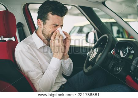 from a young man with handkerchief. Sick guy has runny nose. man makes a cure for the common cold in the car.
