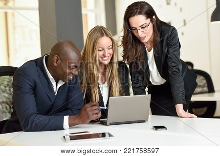 Multi-ethnic group of three businesspeople meeting in a modern office. Two caucasian women and a black man wearing suit looking at a laptop computer.