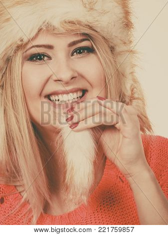 Outfit for cold days ideas, fashion and clothing concept. Attractive smiling blonde woman wearing furry winter hat, hiding behing furr tail