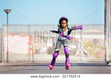Preteen African girl in roller skates and protective gear, riding fast at skate park