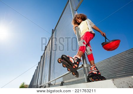 Low-angle view of preteen African girl in roller skates posing at skate park at sunny day