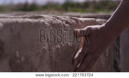 Hand Touch Stone Wall. Hand Mans Touches The Stone Wall. Man Longing For The Native Land And Places,