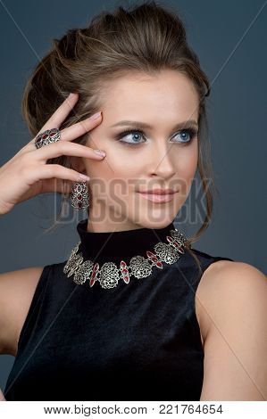 luxury jewelry and fashion concept. A model with earrings necklace and ring on gray background