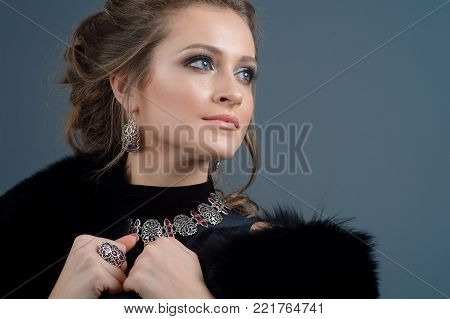 Model in set of jewelery. Beautiful woman in a necklace, earrings and big ring. Beauty and accessories.