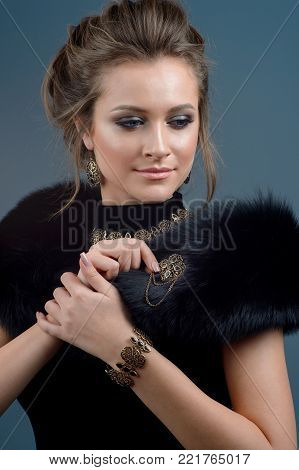 Glamourous Retro Woman Portrait. Beauty Glamour Lady. Jewelry brooch earrings and necklace. Vintage styled Girl with perfect make up and hairstyle. Luxury Accessories.  Jewelry  of bronze