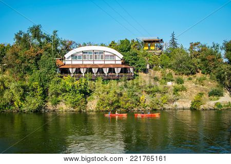Park Monastery Island, Dnepropetrovsk. Restaurant, cable car, floating kayaks, green trees, River Dnepr. Blue water, sky, early autumn