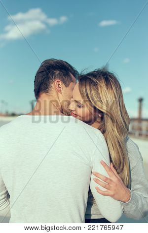 Young casual couple embracing whispering love to each others outdoors