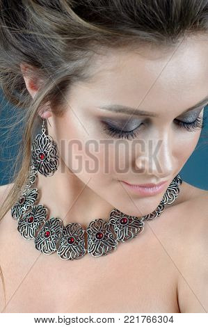 Portrait of young beautiful woman with brown hair fresh skin wearing accessories and jewelry isolated over dark blue background