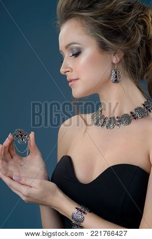 Beautiful woman showing off her jewelery in fashion concept wearing accessories and jewelry isolated over dark blue background